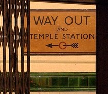 "Station sign seen through lift: ""Way Out and Temple station"""