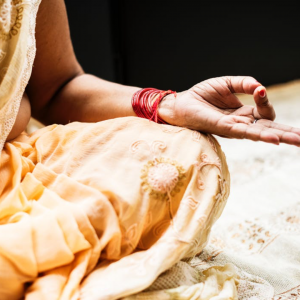 Image of a woman's hand on her knee, wearing rakhi and sari